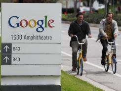 Google workers ride bikes outside of Google headquarters in Mountain View, Calif.