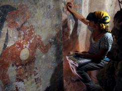 Conservator Angelyn Bass cleans and stabilizes the surface of a wall of a Maya house that dates to the 9th century A.D.