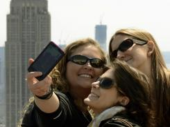 Three women take a photo of themselves with a view of the Empire State Building.