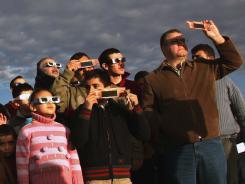 Residents watch a solar eclipse in Amman, Jordan Friday Jan. 15, 2010.