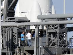 Workers examine SpaceX's Falcon 9 rocket after its aborted launch attempt from Cape Canaveral Air Force Station Saturday. SpaceX will try to launch the rocket again early Tuesday morning.