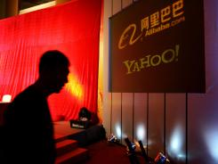 In this file photo, a man walks past a screen displaying the Yahoo and Ali Baba.com logos.