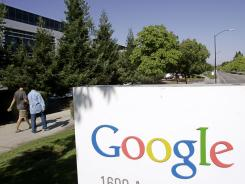 Google workers walk by a Google sign at company headquarters in Mountain View, Calif.