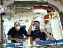 In this frame grab from a NASA video, NASA astronaut Don Pettit, left, and Russian cosmonaut Oleg Kononenko enter the SpaceX Dragon capsule for initial inspections.