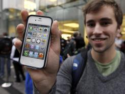 Elliott Johns, of Boston, holds up an iPhone 4S in front of an Apple Store.