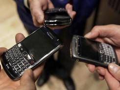 Three people on the floor of the New York Stock Exchange display their Blackberry smartphones.