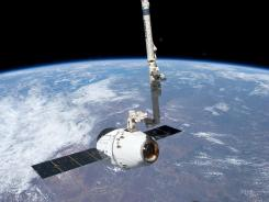 The SpaceX Dragon commercial cargo craft is held by the Canadarm2 robotic arm Friday at the International Space Station.