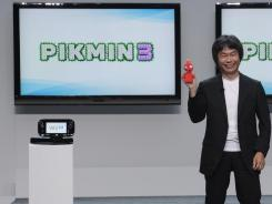 Shigeru Miyamoto of Nintendo holds up a stuffed character from the new video game 'Pikmin 3' during the company's press briefing.