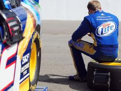 Driver Brad Keselowski sits on a tire and uses his cellphone during a recent practice.