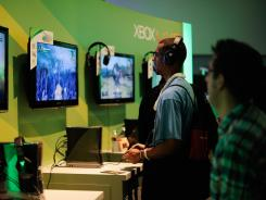 Attendees play a video game in the Xbox Microsoft booth during the E3 gaming conference on June 5, 2012 in Los Angeles.