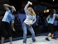 Efthemia Papadopoulos, center, tries out Just Dance 4 with Nintendo's Kamri Collins, left, and Alyssa Marchall during E3.