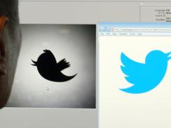A man looks at a computer monitor showing the and old (left) and new Twitter logos.
