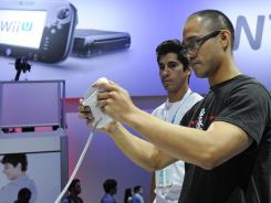 Michael Altamirano tries out the upcoming Wii U under the guidance of Timothy Gonzales of Nintendo during this month's E3 video game conference.