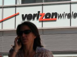A pedestrian talks on a cellphone as she walks by a Verizon Wireless store in New York City.
