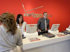 Verizon workers help customers at a Verizon store in Mountain View, Calif.