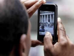 A tourist uses his iPhone to photograph Federal Hall in New York's Financial District.