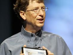 "Microsoft founder Bill Gates shows a prototype of an ""ultra-mobile"" Tablet PC at an event in April 2005."