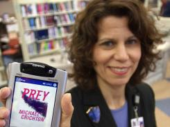 "In a 2003 photo Sari Feldman, deputy director of the Cleveland Public Library, holds a PDA containing Michael Crichton's book ""Prey,"" at the downtown Cleveland branch."