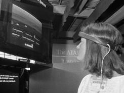 In this June 5, 1984, file photo, a woman in Chicago demonstrates Atari's Mind Link game.