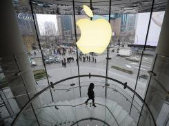 A customer walks under an Apple logo sign at an Apple shop in Shanghai.