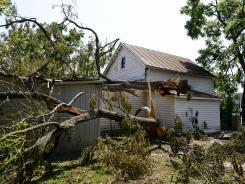 A tree lays across part of the top of a building behind the Virginia Quilt Museum in Harrisonburg, Va. on July 5, 2012.