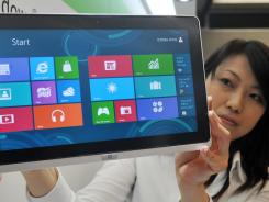 A woman displays a tablet computer running Windows 8.