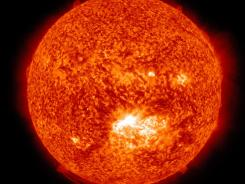 This NASA image shows a solar flare, lower center, erupting from the sun on Thursday. Space weather scientists said there should be little impact to Earth.