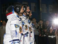 From left, Japanese astronaut Akihito Hoshide, Russian cosmonaut Yuri Malenchenko and U.S. astronaut Sunita Williams stand together before the mission to the International Space Station.