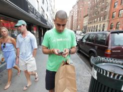 Neville Clubwala, a Taskrabbit worker in New York City, delivers cupcakes from Butter Lane bakery and champagne, to a recipient who received a promotion.