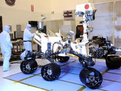 Technicians inspect the Mars rover Curiosity at Kennedy Space Center in Cape Canaveral on Aug. 12, 2011. The rover is expected to land on Mars next month.