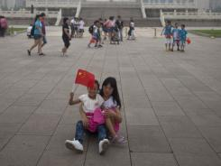 A girl waves Chinese national flag while resting with her mom in front of the Monument to People's Heroes on the Tiananmen Square in Beijing, China.