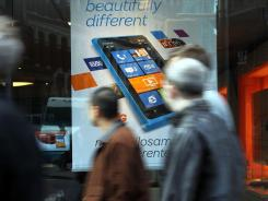 People walk past an advertisement for the Nokia Lumia 900 phone in the window of an AT&T store.