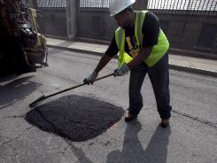 Boston Public Works worker Tyrone Odom, of Boston, fills a pothole with asphalt in Boston's Charlestown neighborhood.