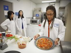 Lockeed Martin senior research scientist Maya Cooper shows a vegan pizza developed at NASA's Advanced Food Technology Project at Johnson Space Center in Houston Tuesday, July 3, 2012.