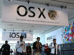 Attendees walk by posters for the new OSX Mountain Lion operating system at the Apple 2012 World Wide Developers Conference.