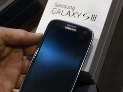 A Samsung Galaxy S III phone is held by a customer at Best Buy in Mountain View, Calif.