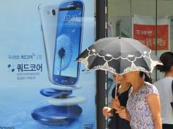 Pedestrians walk past a shop offering South Korea's Samsung Electronics's Galaxy S III phone along a street in Seoul.
