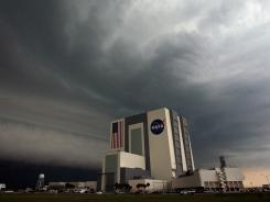 A large thunder storm moves over NASA's Vehicle Assembly Building.