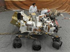 NASA engineers James Wong, left, and Errin Dalshaug examine a model of the Mars rover Curiosity in Pasadena, Calif., on Aug. 2.