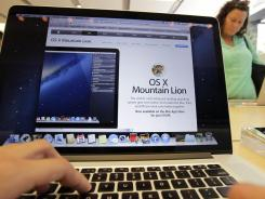 A customer looks at the new OS X Mountain Lion operating system at an Apple store in Palo Alto, Calif.