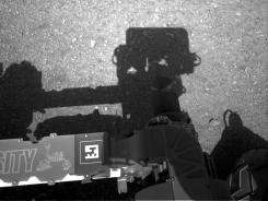 A camera on the Curiosity rover shows the shadow of the rover's now-upright mast in the center, and the arm's shadow at left. The navigation camera is used to help find the sun.