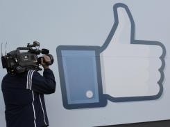 "A television photographer shoots the ""like"" sign outside of Facebook headquarters in Menlo Park, Calif."