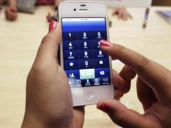 A customer uses an Apple iPhone 4S at an Apple store in Palo Alto, Calif.
