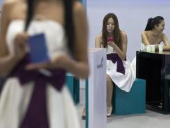 A model checks her mobile phone while taking a break at an exhibitor's booth Aug. 2 at the Macworld iWorld expo in Beijing.