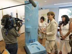 """Tove Larsen, second from right, of Eawag, the Swiss Federal Institute of Aquatic Science and Technology, talks about their diversion toilet at the """"Reinventing the Toilet"""" Fair on Tuesday in Seattle."""