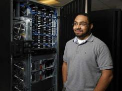 Compuware intern Thyrus Gorges, 20, of Detroit stands near a mainframe computer hard drive deck. He is among the students who completed a Compuware and Wayne State University College of Engineering training course on the technology.