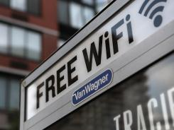 A free Wi-Fi hotspot beams broadband internet from atop a public phone booth in Manhattan.