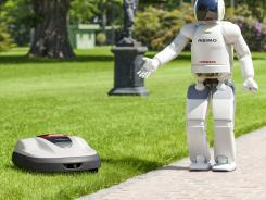 In this undated photo released by Honda Motor, its Asimo walking talking robot shows its new product lawn mower Milmo.