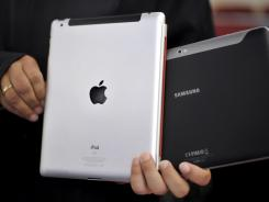 An attorney holds an Apple iPad, left, and a Samsung Galaxy Tab 10.1 at a regional court in Duesseldorf, Germany.