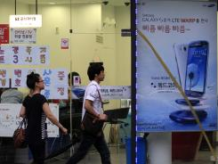 People walk past by banners advertising Samsung and Apple's smart phones at a mobile phone shop in Seoul, South Korea, Aug. 28, 2012.